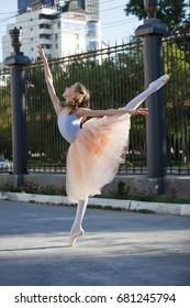 Young beautiful ballerina dancing outdoors in a park. Full length portrait beautiful blond caucasian girl.