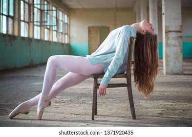 Young, beautiful ballerina in an old building posing on the chair Young, elegant, graceful woman ballet dancer