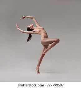 young beautiful ballet dancer in beige swimsuit posing on grey gradient studio background