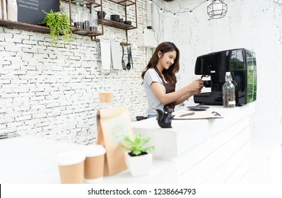Young beautiful barista female in an apron preparing cup of coffee for customer in coffee shop. Woman startup business owner and SME Concept.