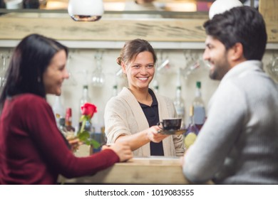 Young and beautiful barista serving coffee to couple