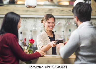 Young and beautiful barista serving coffee to customers