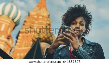 7e0cf497c44 Young beautiful biracial tourist girl with curly afro hair talking with her  family via smart phone