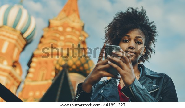 Young beautiful biracial tourist girl with curly afro hair talking with her family via smart phone while standing in front of Saint Basil's Cathedral in Russia, Moscow on sunny summer evening