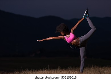 young beautiful black woman doing yoga exercises in the nature of a beautiful summer night