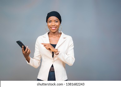 young beautiful black woman smiling and pointing to her mobile phone held in her other hand instructing viewers to use their phones