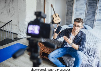 The young beautiful blogger guy recording to the video camera a review of the new mobile phone for his followers, in a loft room.