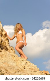 young and beautiful blond girl between yellow rocks against blue sky