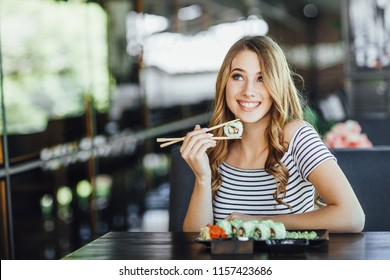 A young beautiful blond girl eating sushi on the summer terrace of a Japanese restaurant