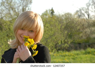 Young beautiful blond girl holding dandelion`s bouquet