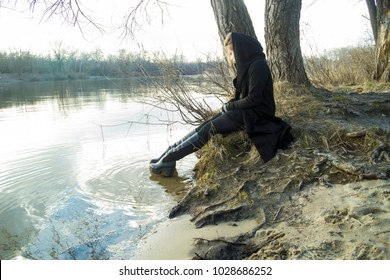 Young beautiful blond haired girl dressed in black clothes stands and sits on the river bank.