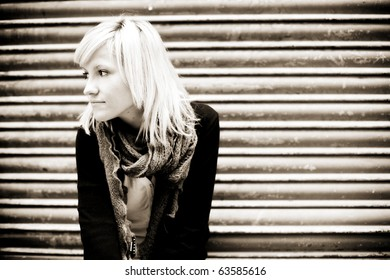 Young beautiful blond portrait on urban background.