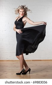Young beautiful blond woman in black dress is dancing.