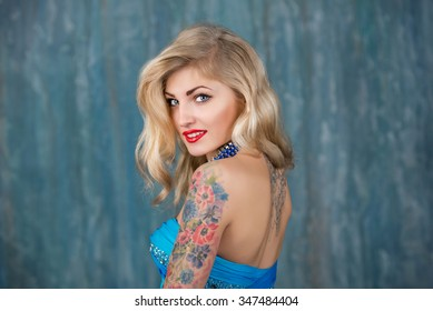 young beautiful blond woman in the blue dress. Girl with  a tattoo on his shoulder, red lipstick, dark background