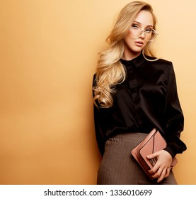 Young beautiful blond woman in a brown blouse and pants holds a handbag and posing on a beige background.Fashion style.