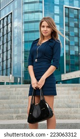 Young beautiful blond woman in dark blue dress near office building