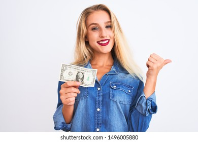 Young beautiful blond woman holding dollar standing over isolated white background pointing and showing with thumb up to the side with happy face smiling