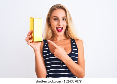 Young beautiful blond woman holding gold ingot standing over isolated white background very happy pointing with hand and finger