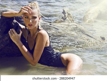 Young beautiful blond woman lies on the wood which is in the sea. Wet, shiny skin and  wearing black swimsuit.