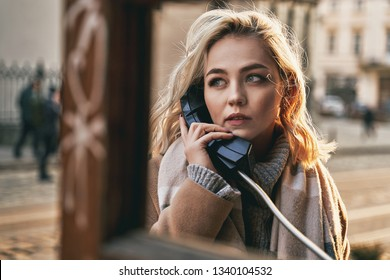 Young beautiful blond woman making an important call in a vintage public phone booth on a sunny evening in golden backlight