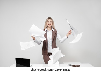 Young beautiful blond woman in an office suit on a white background. Scatters documents. Flying paper