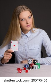 young beautiful blond woman playing poker over grey background