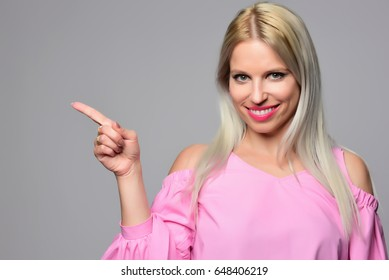 young beautiful blond woman pointing imaginary object. isolated