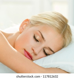 Young beautiful blond woman sleeping on bed
