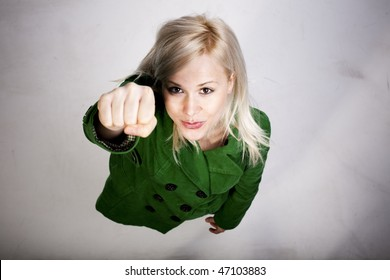 Young beautiful blond woman in a superman pose from above on dirty white floor. Girl power concept