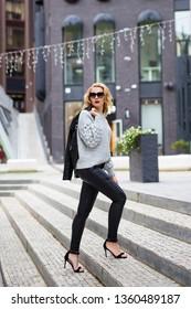 young beautiful blond woman walking in modern city