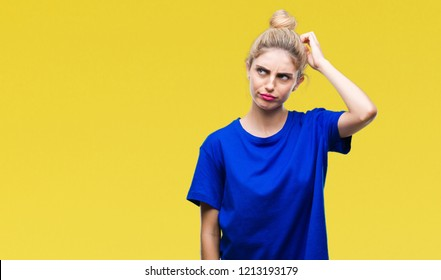 Young beautiful blonde and blue eyes woman wearing blue t-shirt over isolated background confuse and wonder about question. Uncertain with doubt, thinking with hand on head. Pensive concept.
