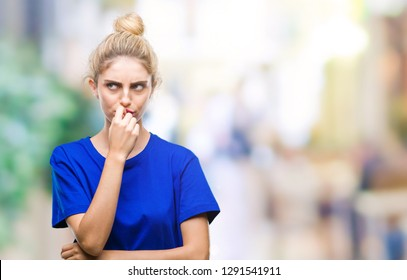 Young beautiful blonde and blue eyes woman wearing blue t-shirt over isolated background looking stressed and nervous with hands on mouth biting nails. Anxiety problem.