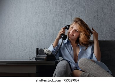 Young beautiful blonde in blue shirt talking on the old phone. Copy space .