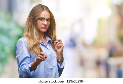 Young beautiful blonde business woman wearing glasses over isolated background disgusted expression, displeased and fearful doing disgust face because aversion reaction. With hands raised. Annoying