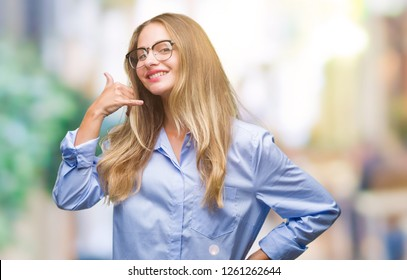 Young beautiful blonde business woman wearing glasses over isolated background smiling doing phone gesture with hand and fingers like talking on the telephone. Communicating concepts.