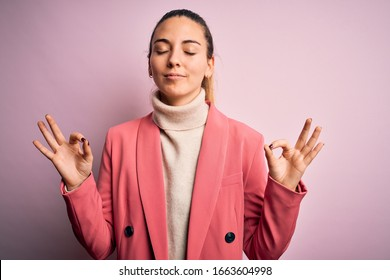 Young beautiful blonde businesswoman with blue eyes wearing elegant pink jacket relax and smiling with eyes closed doing meditation gesture with fingers. Yoga concept.