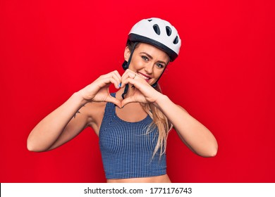Young beautiful blonde cyclist woman wearing bike security helmet over red background smiling in love doing heart symbol shape with hands. Romantic concept.