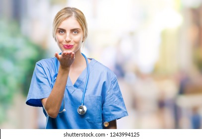 Young beautiful blonde doctor surgeon nurse woman over isolated background looking at the camera blowing a kiss with hand on air being lovely and sexy. Love expression.