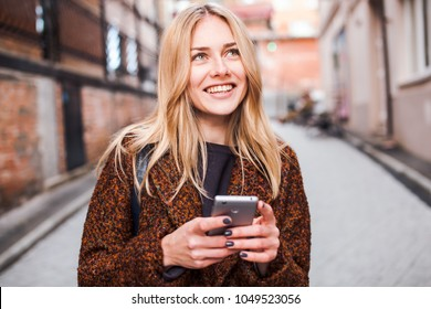 Young beautiful blonde and dreamy woman wearing casual terracotta coat writes sms online with smartphone chatting at street in autumn