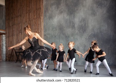young beautiful blonde female ballerina in black scenic gkfnmt, bulky pantyhose and pointe shoes teaches little inattentive girls in black dresses to do bow  dancing Russian ballet in a dance studio