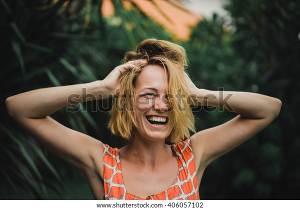 young beautiful blonde girl against the tropical palm trees. beautiful girl with an attractive smile and glowing eyes. emotional portrait of fashion portrait of pretty young hipster blonde. woman.