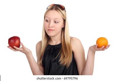 young beautiful blonde girl choosing between apple and orange