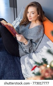 Young beautiful blonde girl cozy on a sofa reading a book near a christmas tree