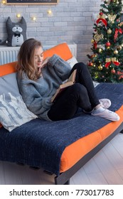 Young beautiful blonde girl. cozy on a sofa. reading a book near a christmas tree.