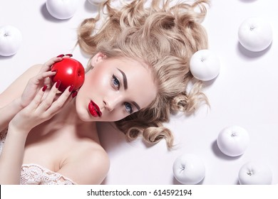 Young beautiful blonde girl with fair skin and red coats lies on white background. A red apple in her  hand, white apples lie around. Snow White. Advertising cosmetics.