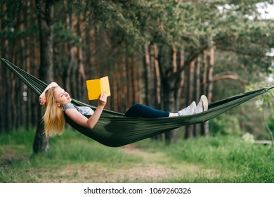 Young beautiful blonde girl in hammock reading e-book. Pretty woman leisure lifestyle portrait at nature ountdoor. Female relax in forest. Adorable teen expressive face. Tourism in summer camp. Hobby