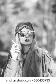 Young beautiful blonde girl holding a cigarette and smokes,black and white photography
