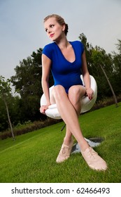 Young beautiful blonde girl sitting on a swivel chair in a garden