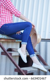 Young beautiful blonde girl is sitting on the stairs at home. Rest on the ranch, outside the city.