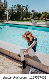 Young beautiful blonde girl smiling by luxurious hotel pool